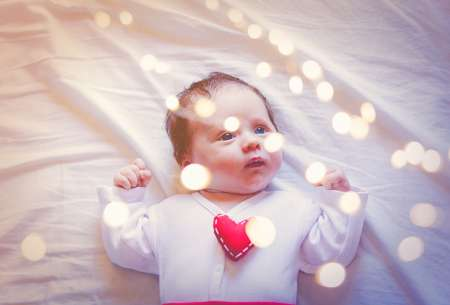 Little infant with heart shape toy on chest and fairy ligths