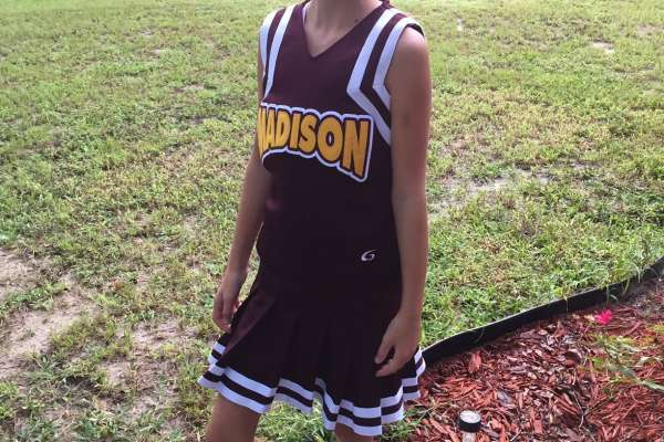 Madison in a burgundy cheerleading outfit posing for the camera